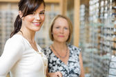 Salesgirl With Senior Woman In Optician Store — Стоковое фото