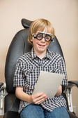 Boy With Trial Frame Reading Test Chart On Chair — Stock Photo