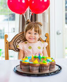 Happy Girl Sitting In Front Of Cake At Home — Stock Photo