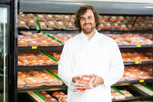 Happy Salesman Holding Meat Packages At Counter — Stock Photo