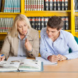 Teacher And Student Looking At Book While Sitting In Library — Stock Photo #35313511