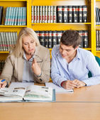 Teacher And Student Looking At Book While Sitting In Library — Stock Photo