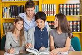Женщина с друзьями, изучает в библиотеке университета — Стоковое фото
