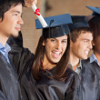 Student Holding Certificate While Standing With Friends At Colle — Stock Photo
