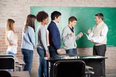 Professor Gesturing Thumbsup To Student In Classroom — Stock Photo