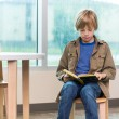 Boy Reading Book In Library — Stock Photo