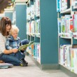 Teacher And Boy Reading Book By Bookshelf — Stock Photo