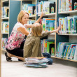 Female Teacher And Boy Selecting Books In Library — Zdjęcie stockowe