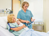 Nurse Explaining Reports On Digital Tablet To Woman With Babygir — Stock Photo