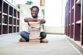 Confident Student With Stacked Books Sitting In Library — Stock Photo