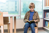 Boy Reading Book In Library — ストック写真