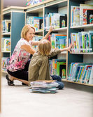 Female Teacher And Boy Selecting Books In Library — Stock Photo