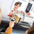 Saleswoman At Counter Attending Customers In Butcher's Shop — Stock Photo