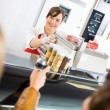 Saleswoman At Counter Attending Customers In Butcher's Shop — Stock Photo #35422089