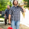 Carpenter And Coworker Carrying Wooden Planks At Construction Si — Stock Photo