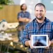 Carpenter Displaying Digital Tablet With Coworker In Background — Stock Photo