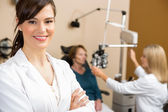 Female Optometrist With Colleague Examining Patient — Stock Photo