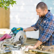 Carpenter Cutting Wood Using Table Saw At Construction Site — Stock Photo
