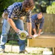 Stock Photo: Carpenter Cutting Wood With Handheld Saw While Coworker Assistin