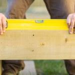 Carpenter's Hands Using Spirit Level On Wood — Stock Photo #35789073
