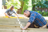 Carpenter Using Drill On Wood At Site — Stock Photo