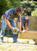 Carpenter Cutting Wood With Handheld Saw While Coworker Assistin — Stock Photo