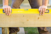 Carpenter's Hands Using Spirit Level On Wood — Stock Photo