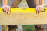 Carpenter's Hands Using Spirit Level On Wood — Stock Photo