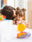 Mother Kissing Girl Eating Cupcake — Stock Photo