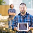 Stock Photo: Confident Carpenter Displaying Digital Tablet With Coworker In B