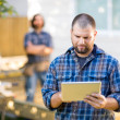 Manual Worker Using Digital Tablet With Coworker Standing In Bac — Stock Photo