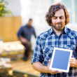 Carpenter Displaying Digital Tablet With Coworker Working In Bac — Stock Photo