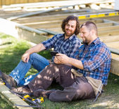 Happy Carpenters Looking At Mobile Phone At Construction Site — Stock Photo