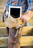 Midsection Of Carpenter With Tablet Computer And Hammer In Toolb — Stock Photo