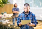ручной работник с помощью цифрового планшета с coworker, стоя в bac — Стоковое фото