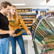 Couple Choosing Meat From Display Cabinet — Stockfoto