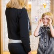 Stock Photo: Boy Looking At Mother While Trying On Spectacles In Shop