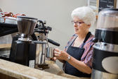 Senior Waitress Steaming Milk In Cafe — Stock Photo