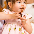 Birthday Girl Eating Cake With Icing On Her Face — Stockfoto