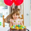 Girl Licking Lips In Front Of Birthday Cake — Stockfoto