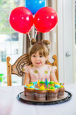 Girl Licking Lips In Front Of Birthday Cake — Stock Photo