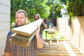 Carpenter And Coworker Carrying Lumbers At Construction Site — Stock Photo