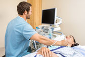 Male Nurse Performing Ultrasound On Patient's Neck — Stock Photo