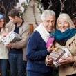 Senior Couple Holding Christmas Presents With Children In Store — Stock Photo