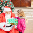 Girl Receiving Present From Santa Claus — Stock Photo