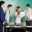Stock Photo: Teacher Gesturing Thumbsdown While Looking At Student In Classro