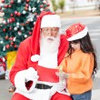 Girl Showing Wish List To Santa Claus — Stock Photo