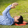 Stock Photo: MUsing Mobilephone While Lying On Grass At Campus