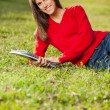 Woman Holding Books While Relaxing On Grass At Campus — Stock Photo