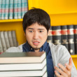 Student Looking At Pile Of Books In University Library — Stock Photo #35907949